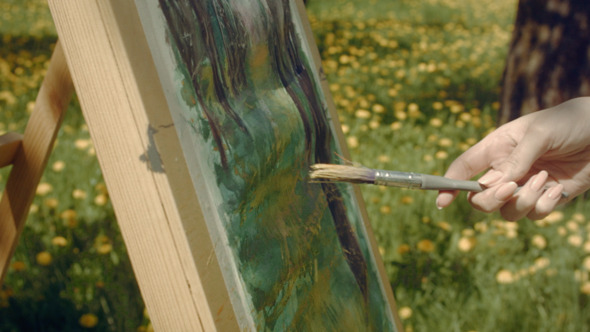 Woman Artist Paints In The Garden