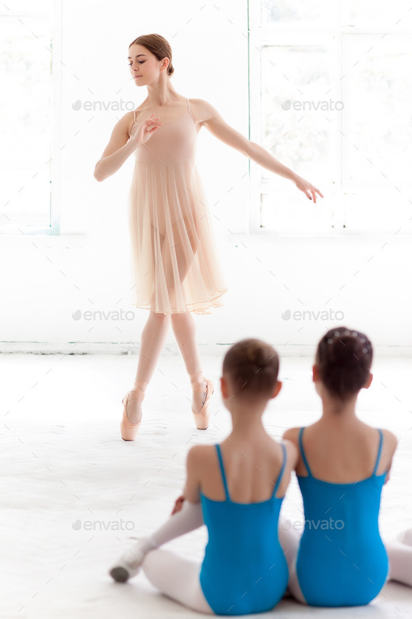 Two little ballerinas dancing with personal ballet teacher in dance studio - Stock Photo - Images