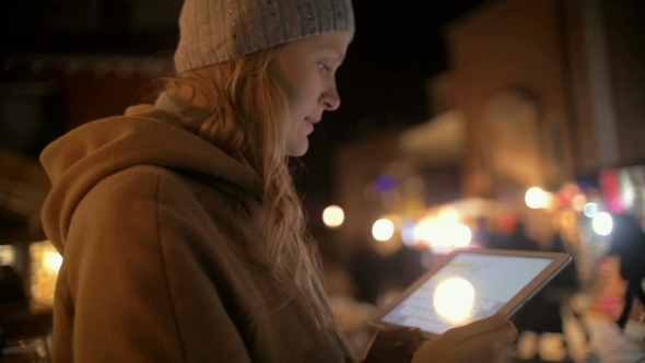 Young Woman Using Tablet PC In The Evening Street