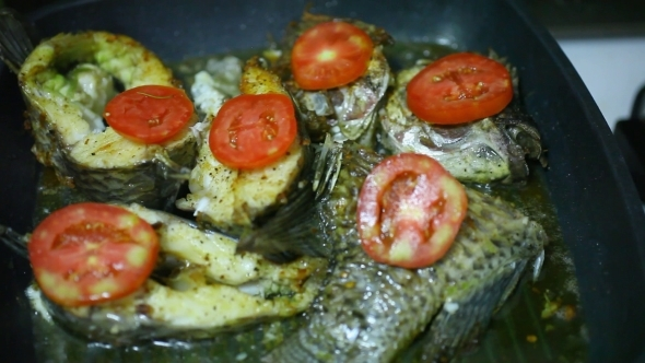Frying Fish In a Grill Pan With Tomatoes Cheese