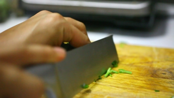 Chopping Parsley On a Wooden Board