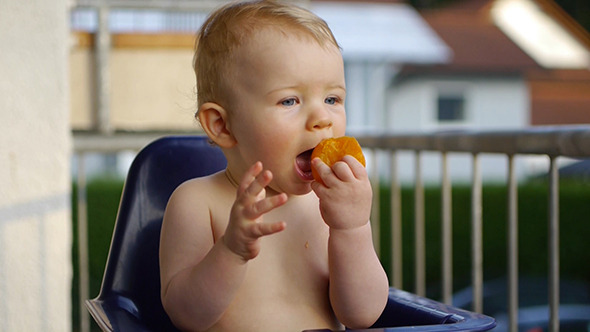 Happy Baby Eating A Peach