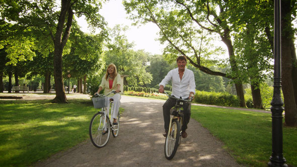 Happy Adult Couple Riding Bicycles in Park