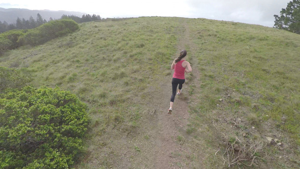 Female Fit Runner Jogging in the Hills