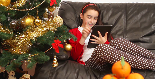 Child Girl with Tablet Pc near Christmas Tree