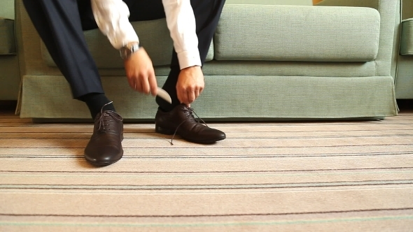 Man Puts On Shoes Focus On The Laces