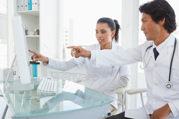 Two doctors pointing to computer screen in an office