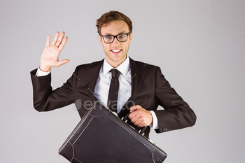 Young geeky businessman holding briefcase on grey background