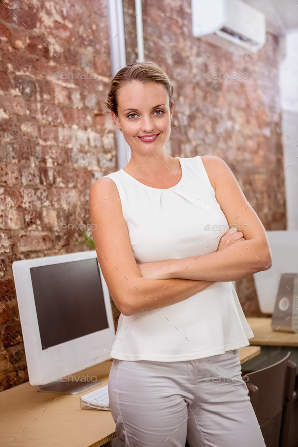 Portrait of beautiful young businesswoman with arms crossed in office - Stock Photo - Images