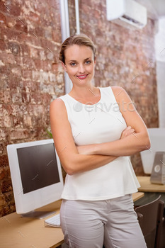 Portrait of beautiful young businesswoman with arms crossed in office