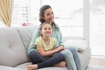 Cute mother and daughter on the couch at home in the living room