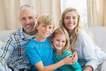 Happy family smiling at camera at home in the living room