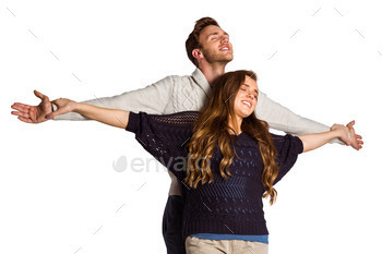 Romantic young couple with arms out standing over white background