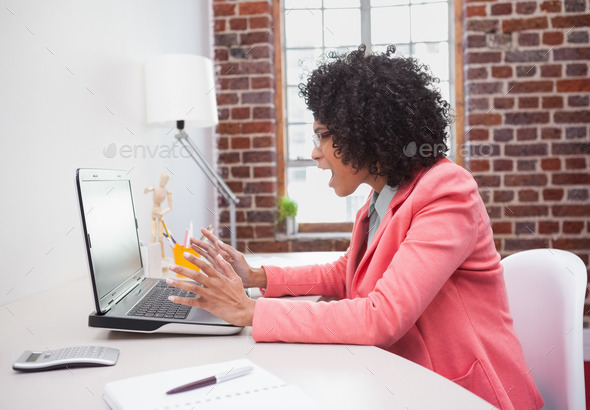 Stressed casual businesswoman sitting at desk in the office - Stock Photo - Images