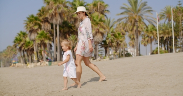 Mother Walking On a Beach With Her Small Daughter