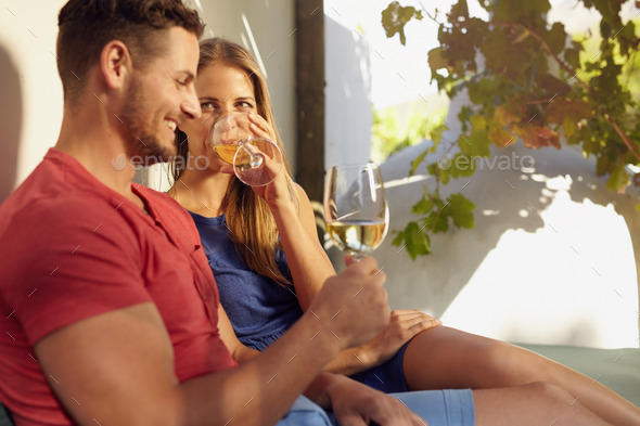 Young couple relaxing outdoors drinking wine - Stock Photo - Images