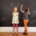 Little girl in front of a blackboard with boy drawing angel wing - PhotoDune Item for Sale