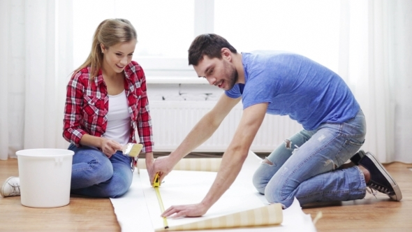 Happy Couple Measuring Wallpaper At Home