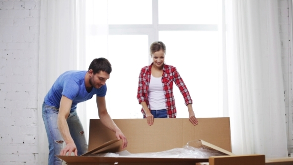 Smiling Couple Opening Big Cardboard Box At Home