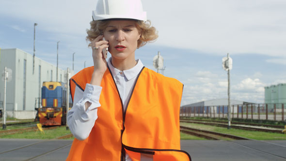 Woman in Hard Hat and Safety Vest Talking on Phone