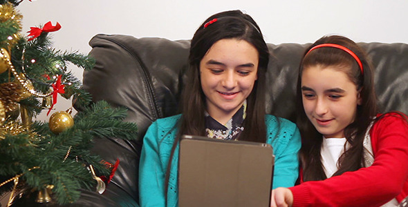 Young Girls Using Tablet near Christmas Tree