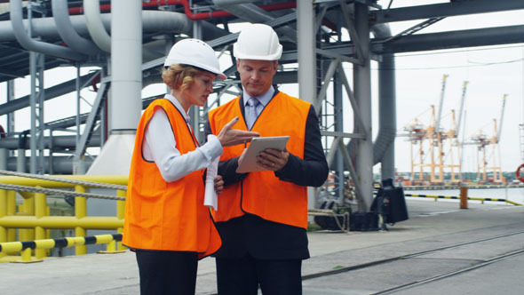 Business People in Safety Vests Using Tablet