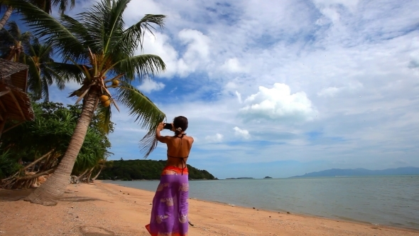 Woman In Pareo Taking Picture Of Exotic Beach With