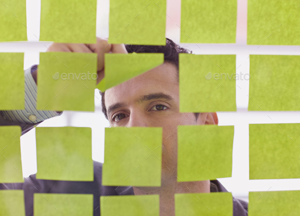 Portrait of a middle eastern business man behind sticky notes in bright glass office - Stock Photo - Images