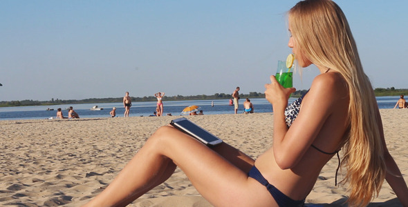 Girl Drinks Cocktail and Using Tablet on the Beach