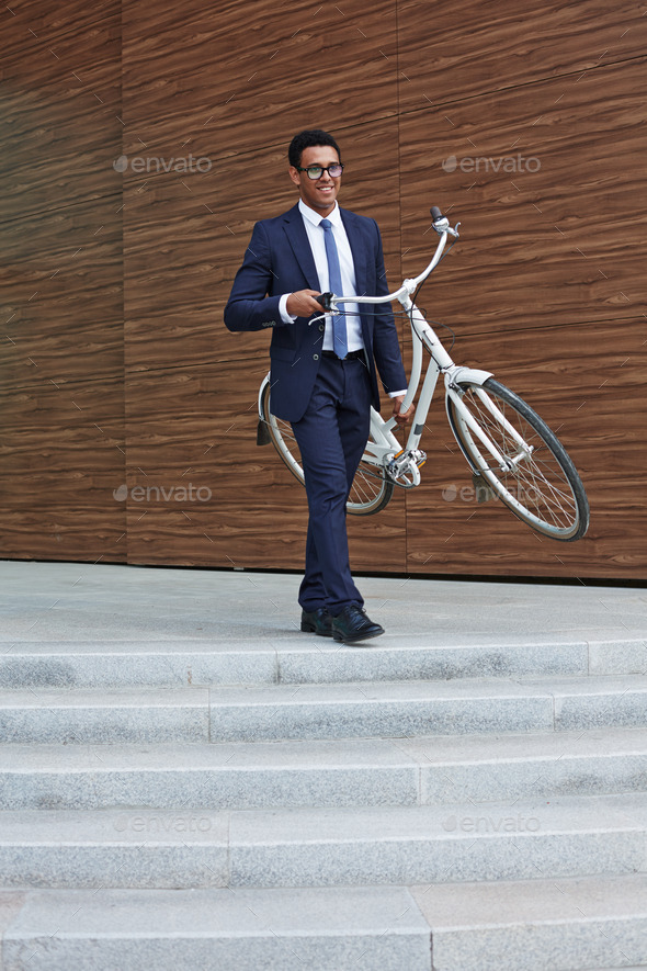 Businessman carrying bicycle - Stock Photo - Images