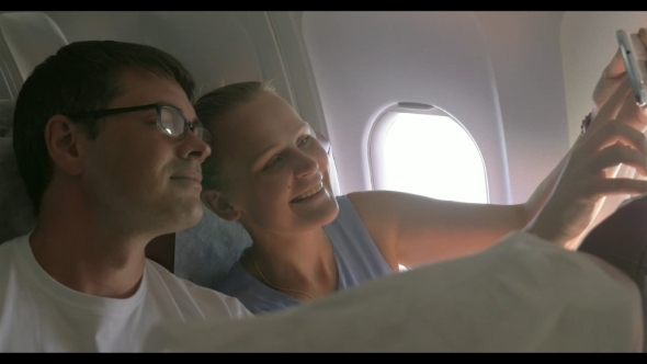 Young Couple Making Selfie With Cell In Plane
