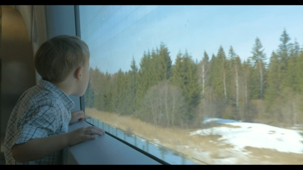 Boy Looking At Nature Scene Through The Train