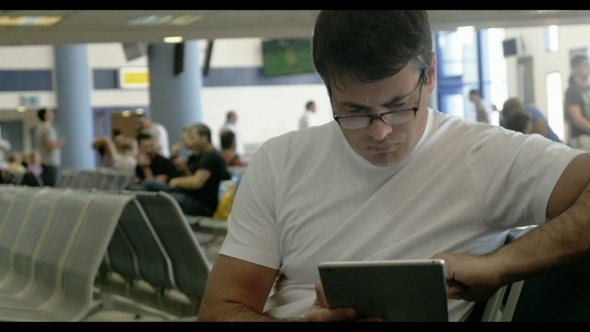 Young Man Working With Touch Pad At The Airport