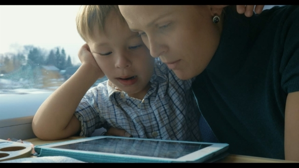 Boy And His Mother Watching Cartooins In Tablet