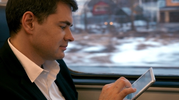 Businessman Traveling By Train With Tablet PC
