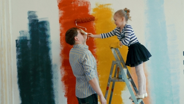 Father And Daughter Painting The Wall