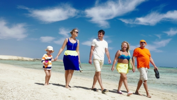 Family Having Enjoyable Walk On The Beach
