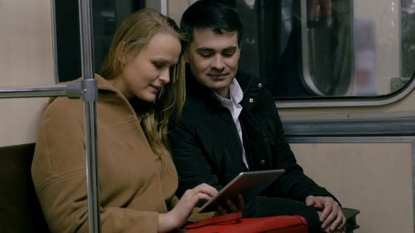 Couple With Tablet PC In Public Transport