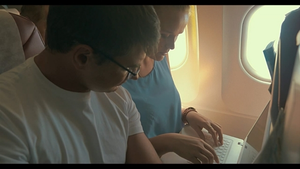 Young People Working With Laptop In Plane
