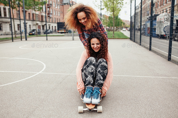 Young girls skating in basketball court - Stock Photo - Images