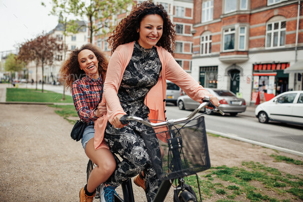 Two young girls having fun on bicycle - Stock Photo - Images