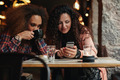 Young friends sitting in a cafe looking at a smartphone - PhotoDune Item for Sale