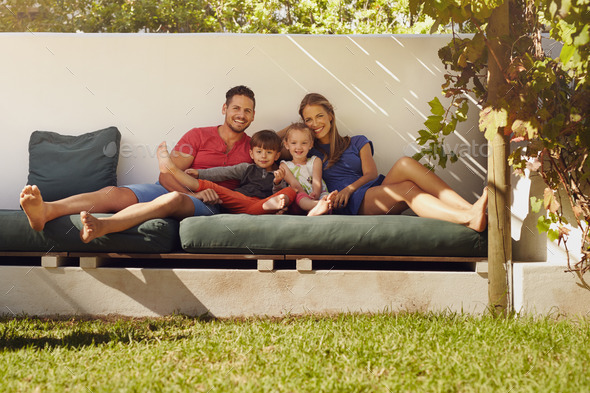 Happy young family sitting on patio - Stock Photo - Images