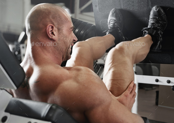 bodybuilder working out at the gym while using fitness machine - Stock Photo - Images