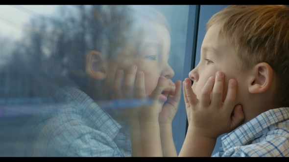 Boy Looking Out The Train Window With Hands On The