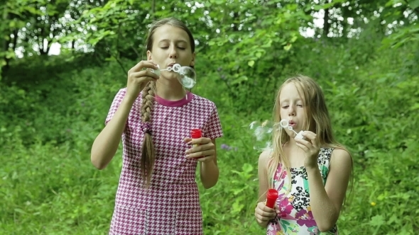 Young Girls Blowing Soap Bubbles Outdoor