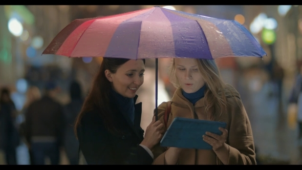 Female Friends Using Touch Pad On Rainy Evening In