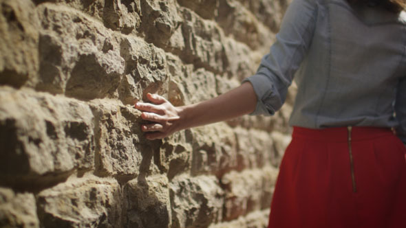 Girl is Walking along Wall and Touching it