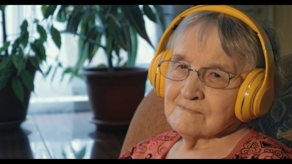 Senior Woman Listening To The Music In Headphones