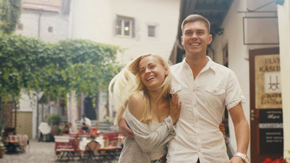 Happy Young Couple is Walking on Streets of Town
